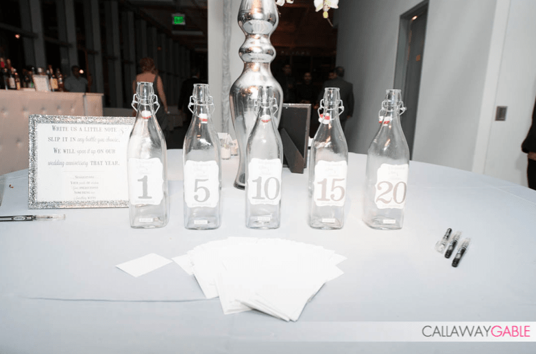 Guests tucked well wishes in bottles that represent milestone anniversaries.  It's a guest book idea that can truly be treasured for years.  www.callawaygable.com