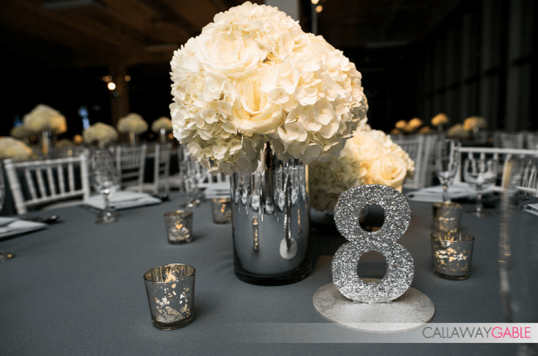 Hydrangea and roses in modern mirror cylinder vases, with glitter table numbers.  Flower Duet florals.  Photo by Callaway Gable.