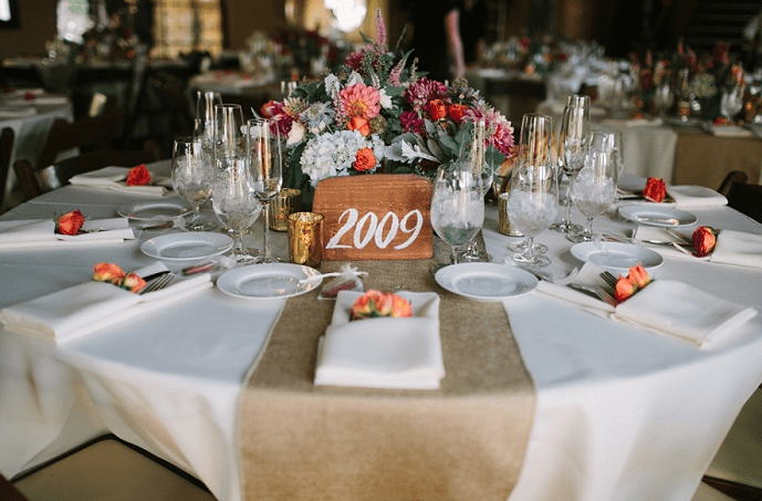 A table featuring burlap runner, a collection of florals by Peony and Plum, and custom wood table number.