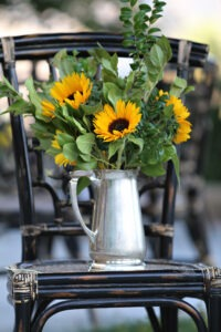 We created this sweet centerpiece with inexpensive greenery and sunflowers, using a pitcher that we sourced from the rental company for that evening's event. Photo by Lorenzo Hodges.