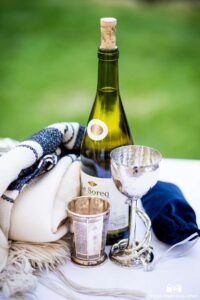 Wine, kiddush cup, tallit, and stomping glass on a ceremony table. Photo by True Photography.