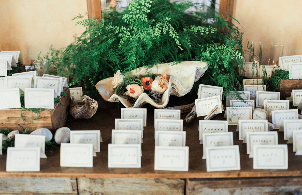 escort card table conch shell rustic wedding fern greenery