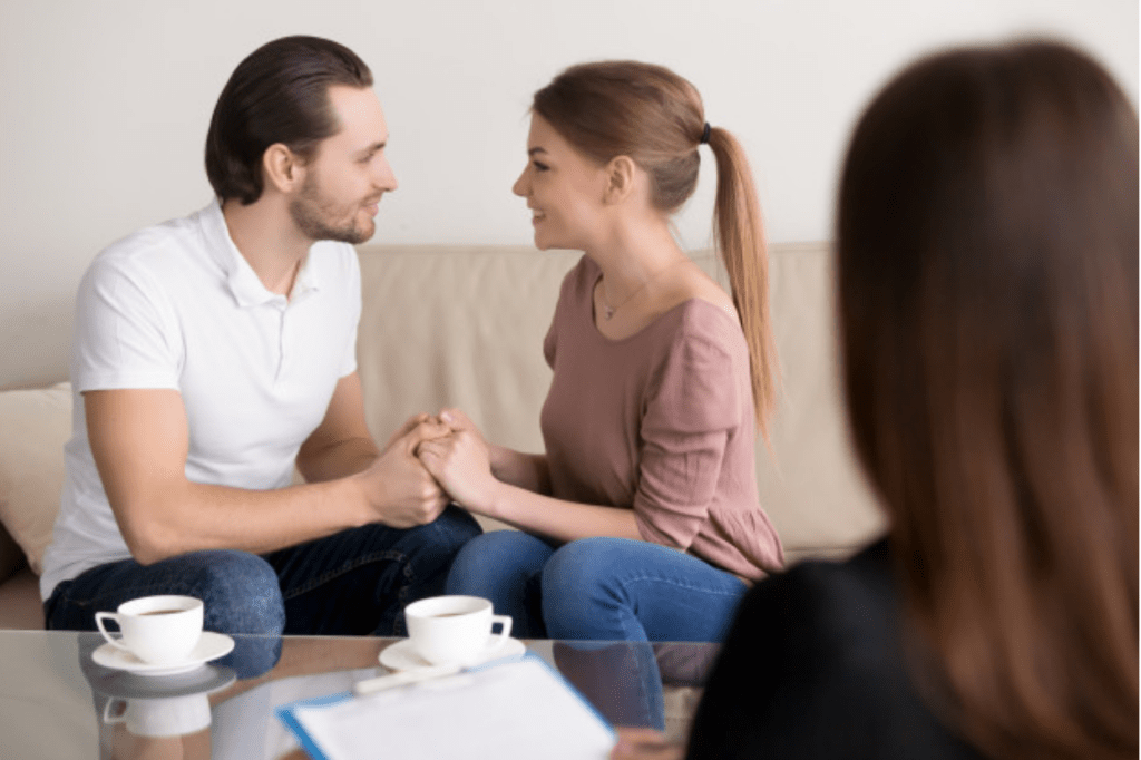 Engaged couple making key decisions about budget with their wedding planner