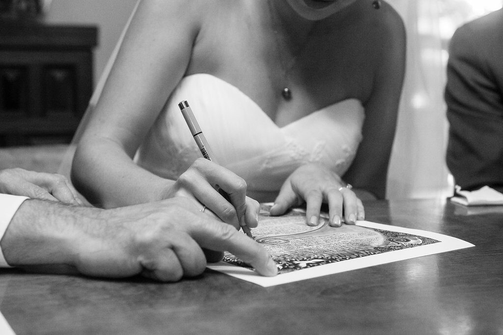 Bride and groom signing ketubah